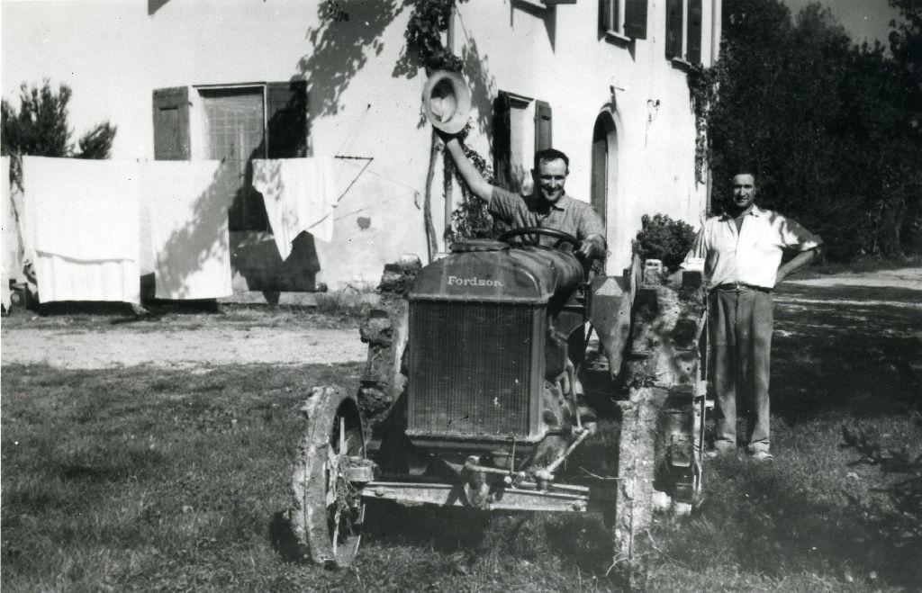 Lavoratori con trattore meccanico Fordson, nell'aia di una casa rurale