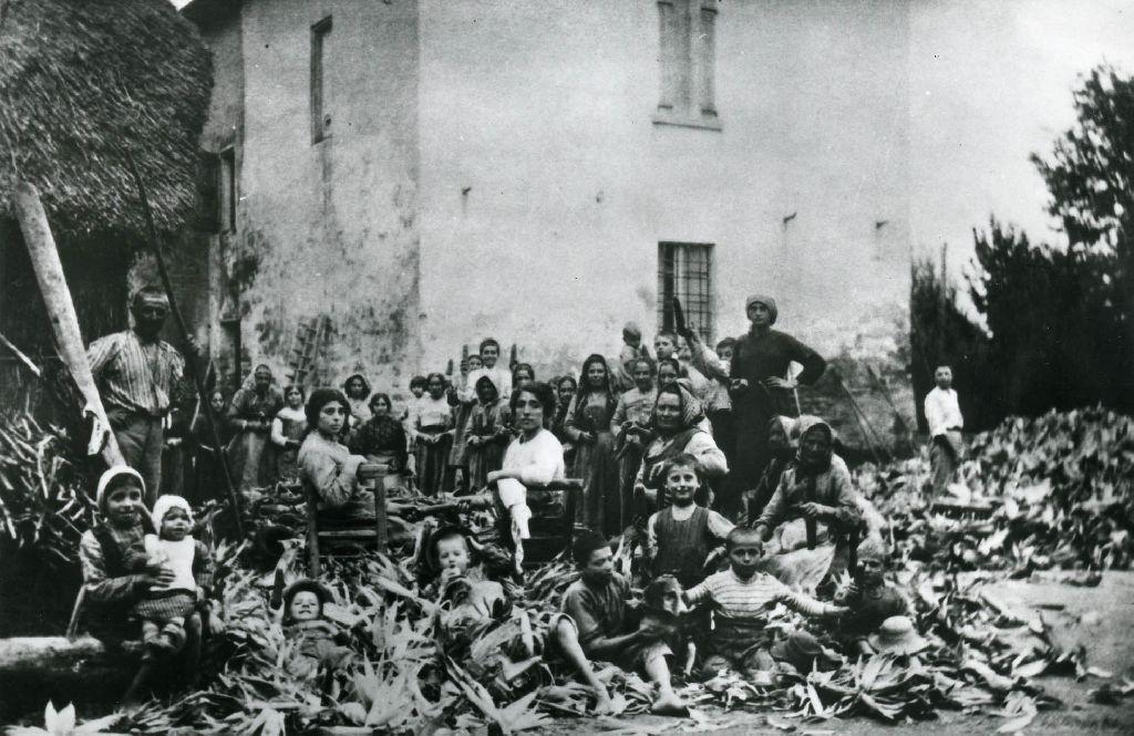 Gruppo di lavoratori intento alla spannocchiatura delle pannocchie di granoturco nell'aia di una casa rurale.