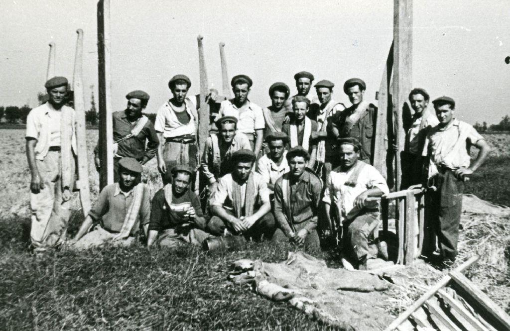 """Gruppo di braccianti della tenuta """"La Bianchina"""" con le barelle per il trasporto dei covoni di riso."""