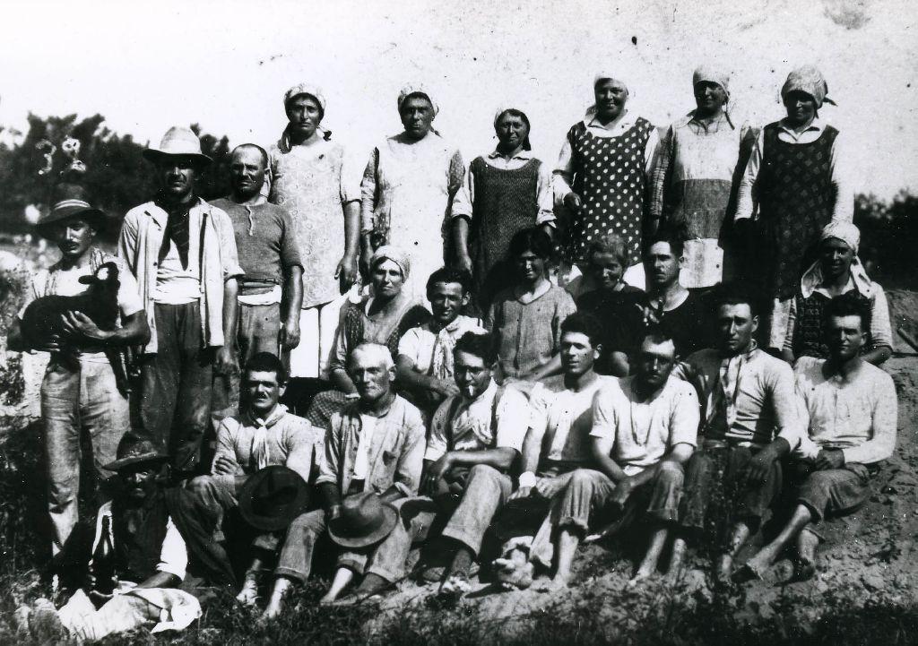 Gruppo di lavoro ritratto durante una pausa. Il primo a sinistra ha in braccio un agnellino