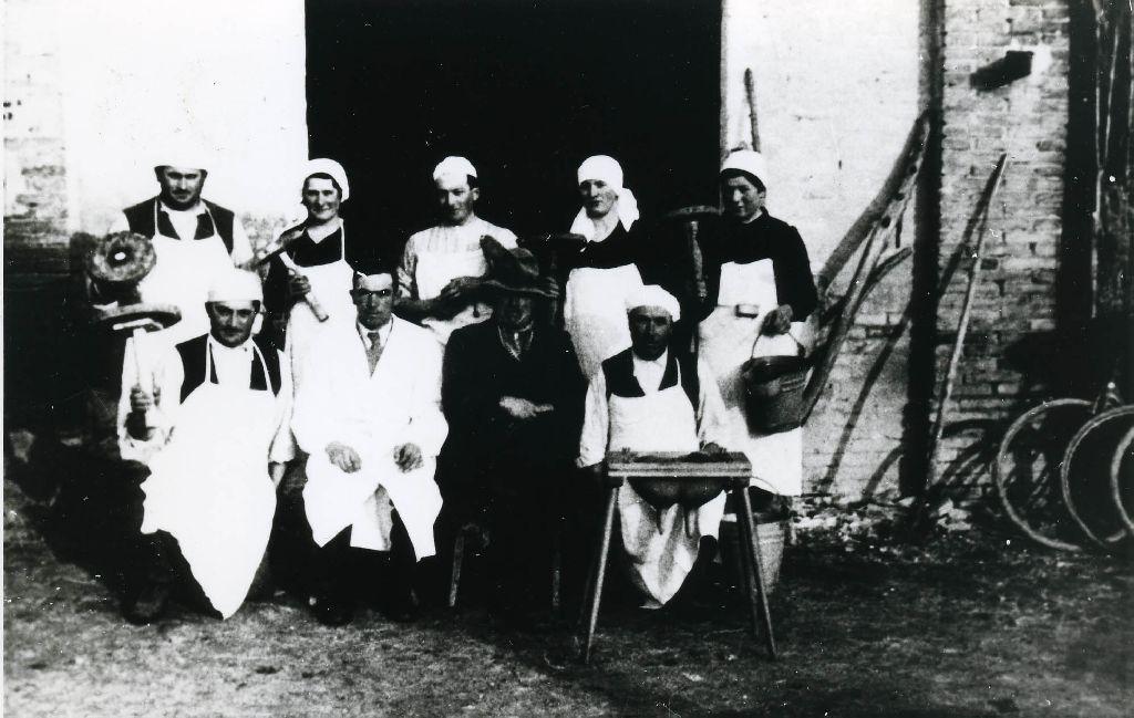 Gruppo di partecipanti ad una scuola di mungitura, ritratto davanti ad una stalla; alcuni anno in mano uno sgabello da mungitura, la ragazza a destra il secchio per la raccolta del latte munto; in basso una riproduzione delle mammelle dell'anima lattifero