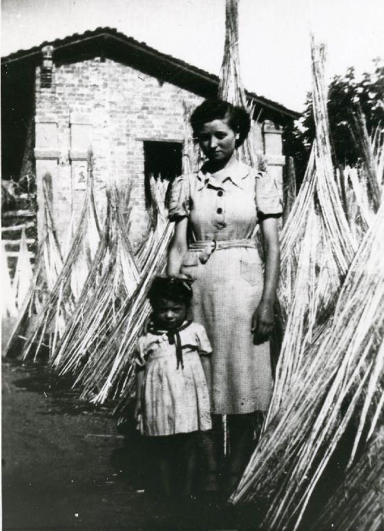 Gina e Gianna Bandiera nel prato di fronte alla stalla-fienile di casa Bandiera, dove sono disposte in forma di cono le mannelle di canapa già macerata per l'asciugatura.