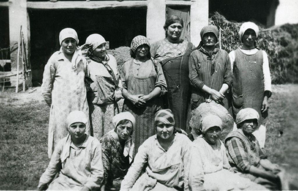Gruppo di sole donne ritratte nell'aia di una casa rurale